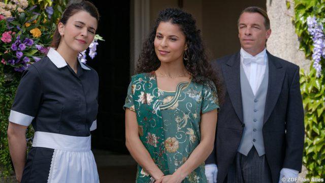 Mit gemischten Gefühlen erwartet Anjali (Patricia Meeden) die Ankunft ihrer Mutter aus Indien. Sie ahnt, warum Gita den weiten Weg nach Cornwall auf sich genommen hat. Hausmädchen Emily (Selma Brook), und der Butler Brad (André Eisermann) warten zusammen mit Anjali.