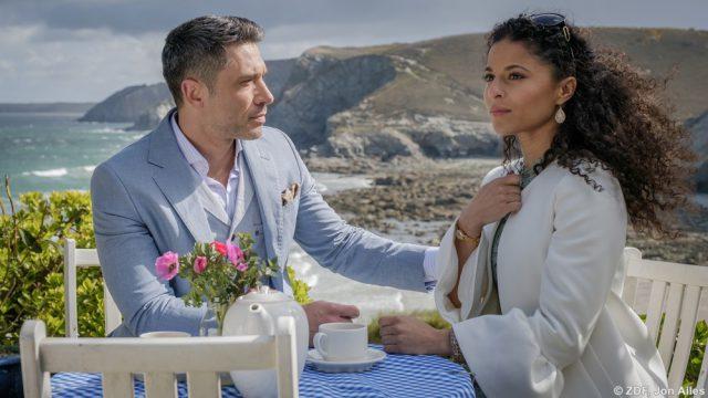"""Ihrer Mutter zuliebe stimmt Anjali (Patricia Meeden) dem Heiratsantrag von John (Jadran Malkovich) zu""""Rosamunde Pilcher: Das Gespenst von Cassley"""": John (Jadran Malkovich) und Anjali (Patricia Meeden) und sitzen an einem Tisch oberhalb des Strands. Vor ihnen steht eine Kaffeegedeck. Anjali hält ihr Medaillon fest und blickt nachdenklich in die Ferne. John hat seine Hand auf ihren Arm gelegt und blickt sie fragend an.."""