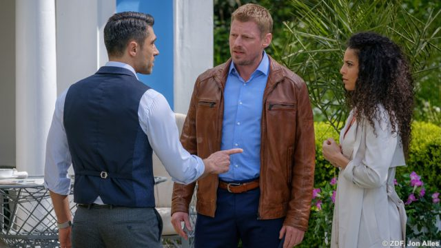 Was hat John (Jadran Malkovich, l.) mit dem tragischen Tod von Anjalis (Patricia Meeden) Ehemann zu tun? Das fragt sich auch Riley (Martin Gruber).